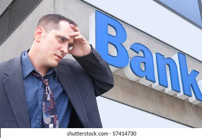 A business man is standing in front of a bank and looks stressed and worried. Can represent finance, the economy, or an investment theme.