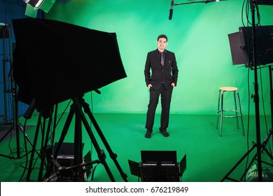 Business man standing up in front of the camera in television studio , Business man presenter in television Studio