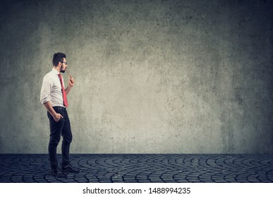 business man standing in front of a wall