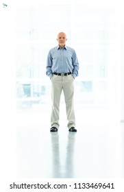 Business man standing with hands in pockets and facing the camera.