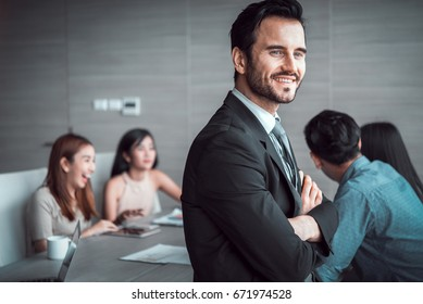 business man standing with his staff in background at meeting room