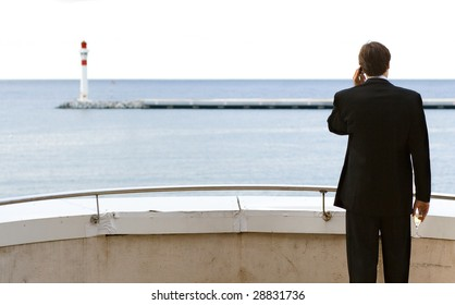 A business man standing on a balcony and talking on the mobile phone with a  glass a21d6c902676