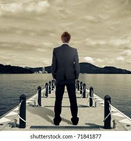 Business man standing on dock near lake.
