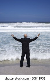 Business man standing on edge of sea, arms outstretched, back view