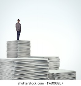 Business man standing on a pile of blank documents