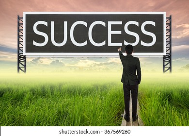 business man standing on wood bridge between rice field and pointing with large sign of success (business concept)