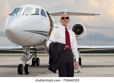 Business man standing outside of an airplane.