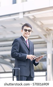 Business man standing outside the office with luggage beside him, just arrive the destination, holding a digital tablet with happiness smiling