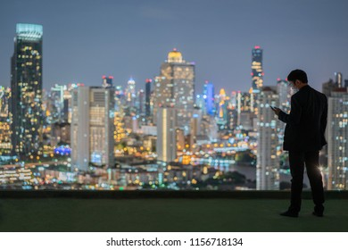 Business man standing over the city at night while looking to his phone