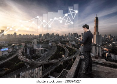 Business man standing over cityscape and business grap,Business Technology and growth concept