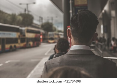 Business man standing in a queue at bus stop, view from the back. Bus terminal near international airport in Hong Kong, China.