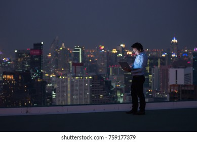 Business man standing while working late by computer laptop on rooftop in the city