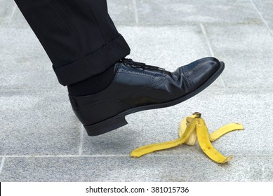 Business man stepping on banana skin peel, work accident concept