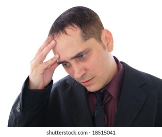 A business man is stressed out and is holding his hand to his forehead.