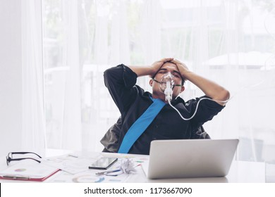 business man is stressed from work To coma use respirator oxygen , laptop and document paperwork on office desk - business concept