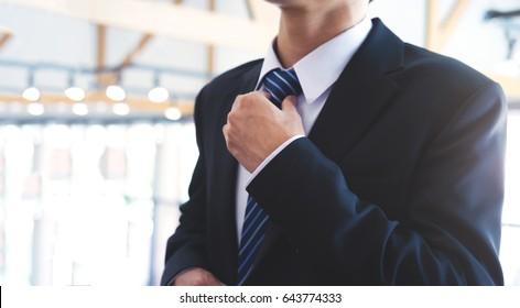 Business man style. Businessman  adjusting his neck tie