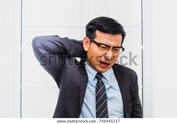 Business man suffering from neck and back pain.