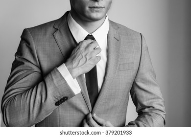 business Man in a suit fixing his tie