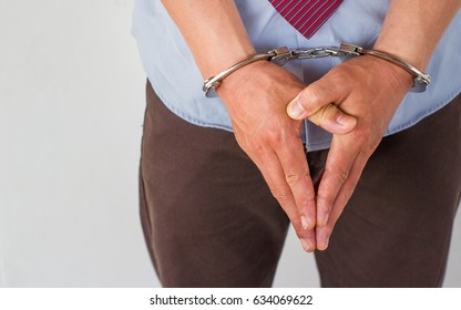 Business man in a suit with handcuffs, under arrest for corruption.