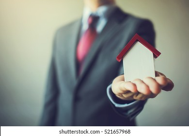 Business man in suit having miniature house on palm of his hand - Business mortgage, property loan, house insurance, business investment concept