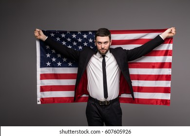 Business man in suit holding USA flag from his back with open mouth isolated gray background