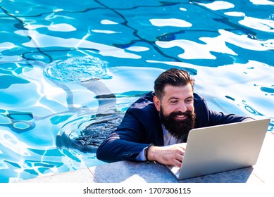 Business man in suit with laptop on swimming pool. Funny businessman relaxing with laptop