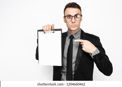 business man in suit, looks surprised, and hold a blank sheet of paper, and points his finger at him, on a white background