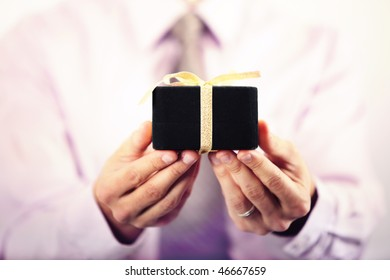 Business man in suit offering gift box straight to the camera