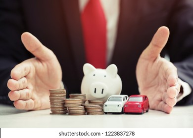 Business man in suit open hand prop up hug model of toy car on over a lot money of stacked coin insurance loan and buying car finance concept. buy and installment down payment a car. Piggy Bank saving
