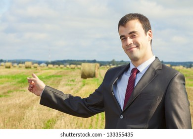 Business man in a suit pointing at copy space