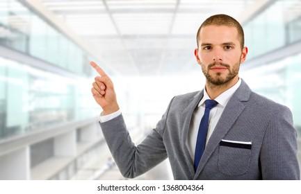 hombre de negocios con traje que apunta con el dedo a la oficina