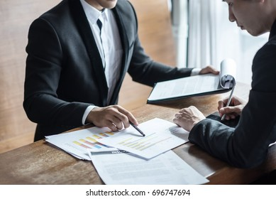 Business man with suit present charts analyzing business model e-commerce sitting desk in office professional team