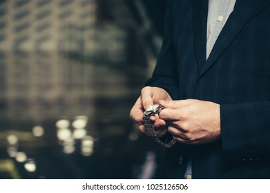 A business man in a suit sets up time in a wrist watch.