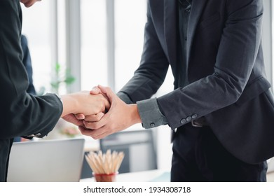 Business man in a suit shakes hands to agree a business partnership agreement. Business etiquette concept of congratulation, concept of handshake during office meeting.
