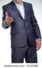 Business man in a suit standing with his hand reaching for a handshake