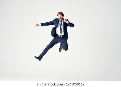 A business man in a suit and tie bounces high