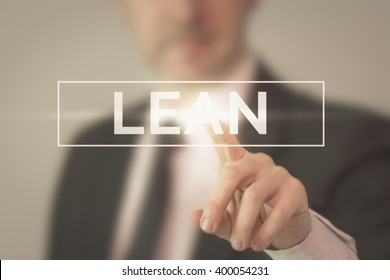 "A business man in a suit touching word ""Lean"" with his finger."