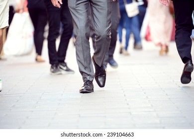 Business man in suit walking on sidewalk