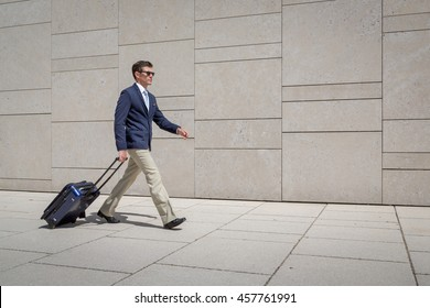 Business man in suit walking with trolley at the airport