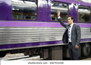 Business man with suit wave hand  at subway. Happy businessman waving his hand to friend on train and say bye bye. Businessman smile greet and say hello friend colleague while standing