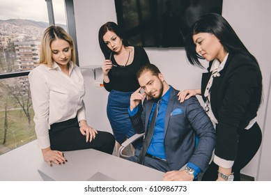 Business man surrounded by his female co-workers