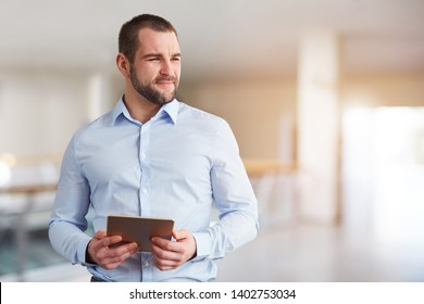 Business man with tablet computer looking to the side in the business center