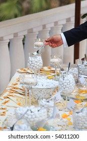 Business man taking candies from wedding buffet