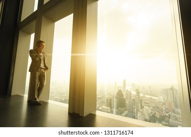 Business man talk via smartphone stand by glass window in tall building with background of city