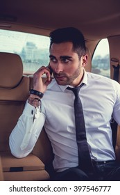 Business man talking by smartphone in the car.