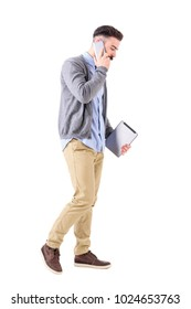 Business man talking on the phone walking and carrying tablet computer looking down. Full body length portrait isolated on white studio background.