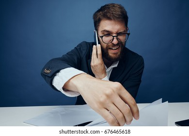 Business man talking on the phone, working with documents, office on a blue background