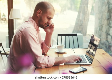 Business man talking on smart phone and look to laptop screen, male freelancer working on computer at wooden table of modern coffee shop loft, young hipster having conversation on cell phone, filter