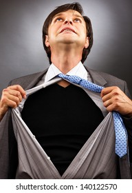Business man tearing off his shirt over gray background