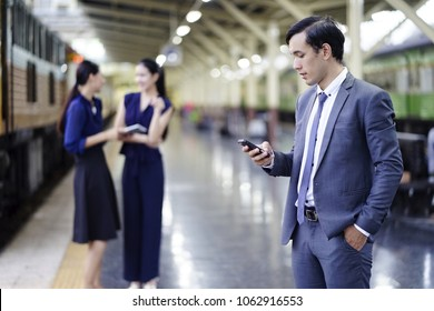 Business man texting on mobile with women and city background.  Serious young businessman holding mobile phone and looking at it while two his colleagues talking to each other in the background.